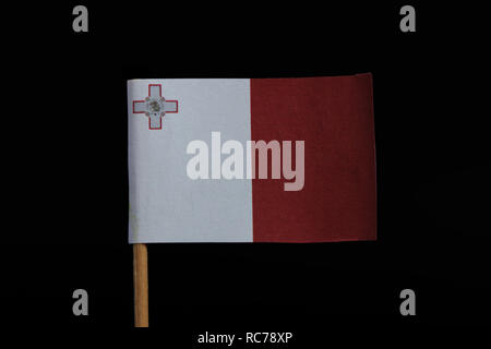 A beautiful and official flag of Malta on toothpick on black background. Vertical bicolor of white and red with the representation of George Cross edg - Stock Photo