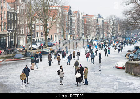 Ice skating people on frozen canal Prinsengracht, Amsterdam, The Netherlands. - Stock Photo