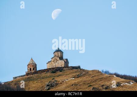 Caucasus mountains, ancient Gergeti Trinity church Tsminda Sameba against blue sky and supermoon, landmark of Georgia - Stock Photo