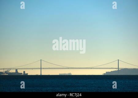 Panoramic view of the 25 de Abril suspension bridge over the Tagus river in Lisbon, Portugal, Europe - Stock Photo