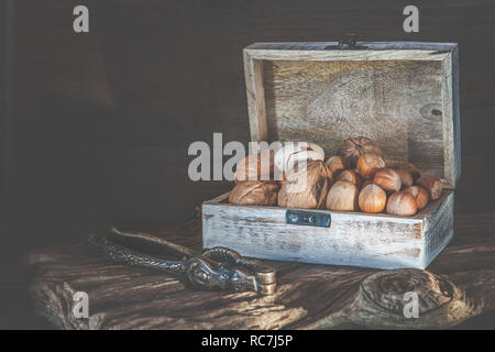 Pecan nuts and macadamia walnuts in a box with pegs for nuts on a wooden background. Copy space. - Stock Photo