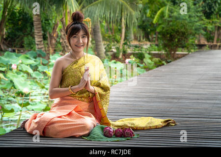 Beautiful asia women wearing traditional Thai dress and sitting on wooden bridge. Her hand is in the respect hands in thailand style. The side has a p - Stock Photo