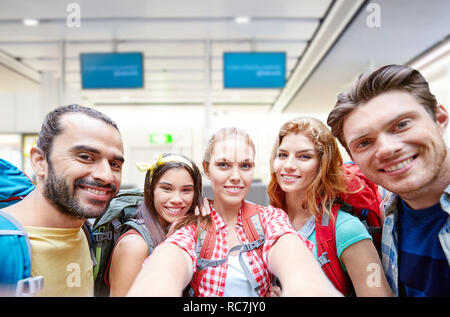 friends or tourists taking selfie over airport - Stock Photo