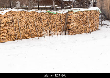 Dry chopped firewood logs stored outside. Dry chopped firewood logs ready stacked out on a snowy day. - Stock Photo