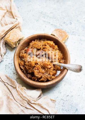 Bowl of cabbage soup with bread roll, still life, overhead view - Stock Photo