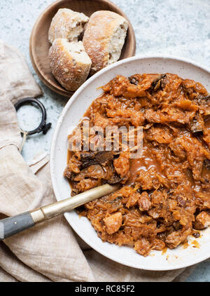 Bowl of cabbage soup with bread rolls, still life, overhead view - Stock Photo