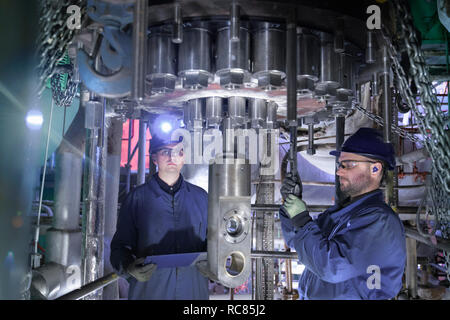 Engineers working in confined space under turbine during outage in nuclear power station - Stock Photo