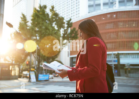 Businesswoman reading newspapers in city, Seoul, South Korea - Stock Photo