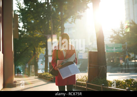 Businesswoman reading newspapers in city, Seoul, South Korea