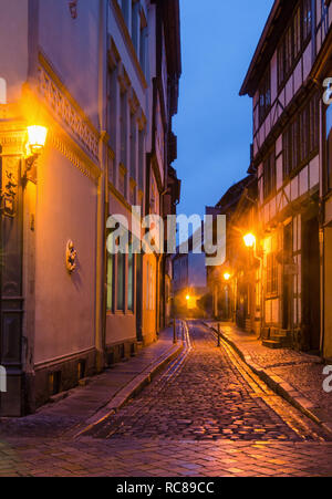 A narrow street along the medieval half-timbered houses in the old town of Quedlinburg illuminated by the warm light of the lamps in the evening - Stock Photo