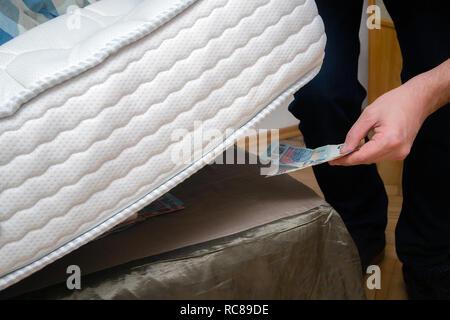 Man putting money under his mattress to save it. Showing no trust in financial institutions and banks, black market - Stock Photo