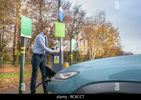 Man charging electric car at charge point, Manchester, UK - Stock Photo