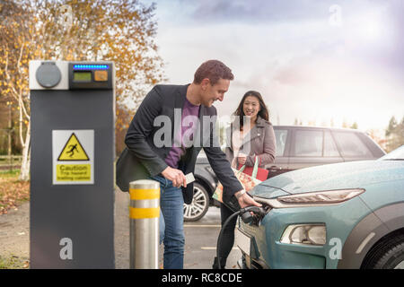 Man and woman charging electric car at car charging park, Manchester, UK