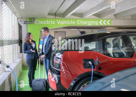 Man and woman charging electric car at charge bay, Manchester, UK - Stock Photo