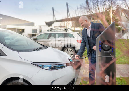 Businessman plugging in electric car at charging point, Manchester, UK - Stock Photo