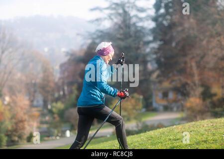 Senior woman nordic walking in park - Stock Photo