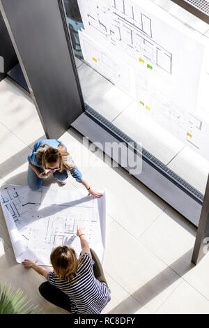 Colleagues brainstorming over plans - Stock Photo