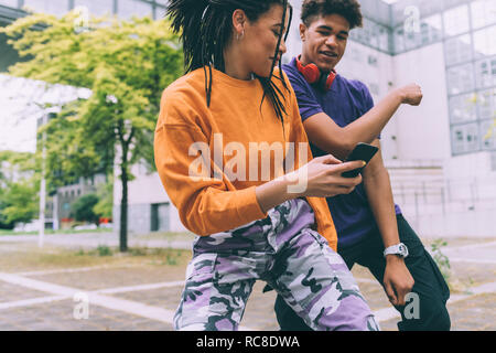 Brother and sister dancing to footage on mobile, Milan, Italy - Stock Photo
