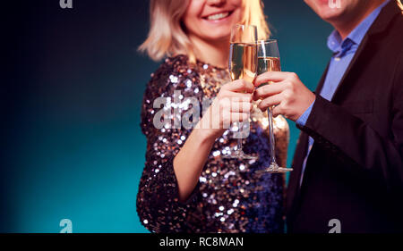 Photo of woman in brilliant dress and men with wine glasses with champagne on blue background - Stock Photo