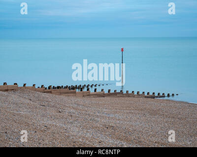 A view of a red marker post and groynes at the sshingle beach at Eastbourne UK on an overcast winter day with muted colours. - Stock Photo