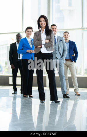 happy young female business leader standing in front of her team. - Stock Photo
