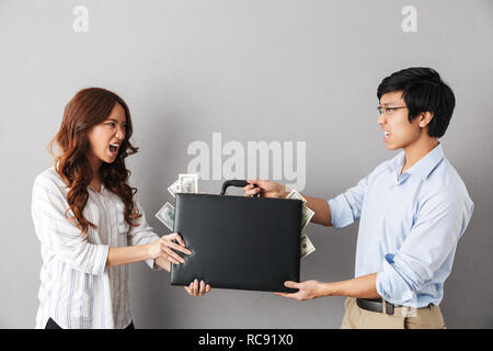 Angry asian couple standing isolated over gray background, fighting for a briefcase full of money banknotes - Stock Photo