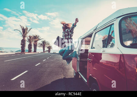 Happiness for travel and enjoying wanderlust concept for beautiful curly crazy woman jumping out the old van with vintage luggage - joyful and success