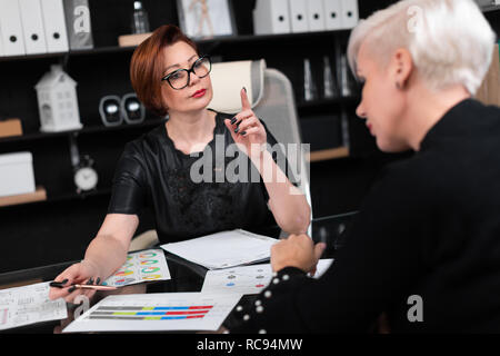 Business women discuss diagrams at Desk in office - Stock Photo