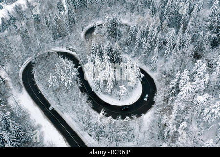 Driving on winter roads trough a forest winding road in the mountains - Stock Photo