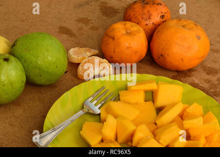 Guava and orange with sliced papaya on a plate with a fork - Stock Photo
