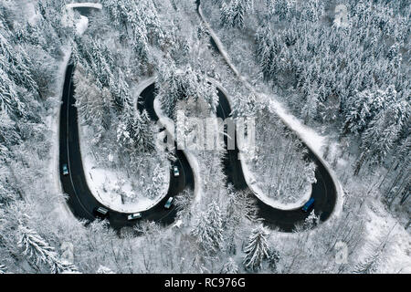 Driving in winter conditions on a highway trough the mountains - Stock Photo