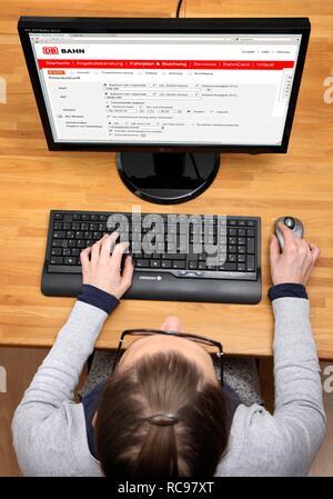 Woman surfing the internet with a computer, Bahn.de, timetable information, ticket booking website of Deutsche Bahn - Stock Photo