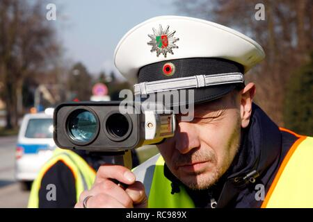 Police officer with a laser speed measuring device, speed check marathon of the police in North Rhine-Westphalia on 10 February - Stock Photo