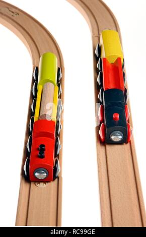Toy wooden trains, two trains on the tracks, symbolic image of a race, competition - Stock Photo