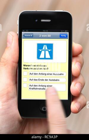 Iphone, smart phone, app on the screen, training for the driving theory test - Stock Photo