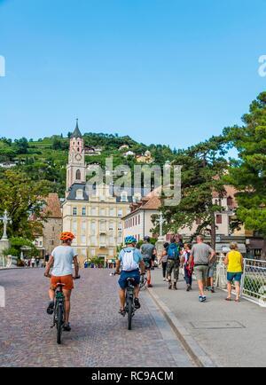 Two cyclists, Passer Promenade, Bolzano Gate, Porta di Bolzano, Saint Nicholas Parish Church, Parrocchia San Nicolò - Stock Photo