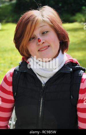 jungendliche Frau mit Marienkäfer auf der Nase | young woman having a beatle on her nose - Stock Photo