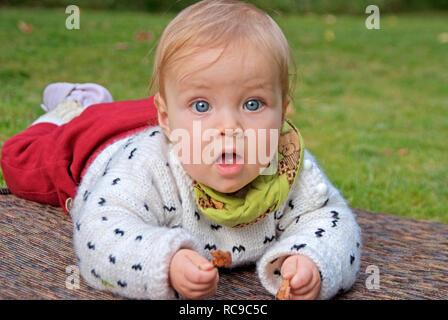Baby liegt draußen auf einer Matte   baby lying outside on a mattress - Stock Photo