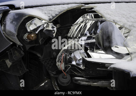Broken car light accident. Close up of damaged headlight in a front of car, winter. - Stock Photo