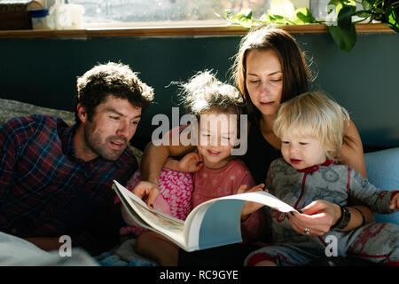 Parents reading to children in bed - Stock Photo