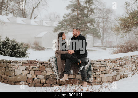 Couple sitting on blanket on stone wall, Georgetown, Canada - Stock Photo