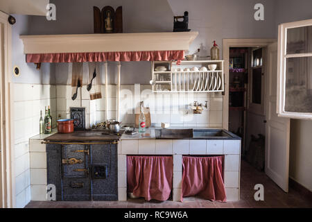 Old cooker with kettles. Kitchen interior with vintage kitchenware. Old pans - Stock Photo