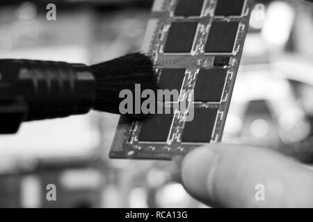 The service center worker cleans dust at Random Access Memory or electronic board RAM - Stock Photo