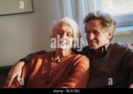 Pärchen mittleren Alters sitzt auf einem Sofa  | middleaged couple is sitting on a couch - Stock Photo