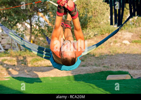 Yoga treatment for core, yoga swing, slim young man strapped to four planks above the ground, man developing endurance and stretching core - Stock Photo