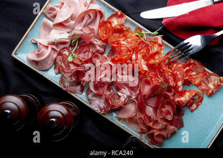 assorted cold meat, prosciutto, slices ham, beef jerky, salami, meat and mustard on black background. Meat appetizer, catering food concept. - Stock Photo