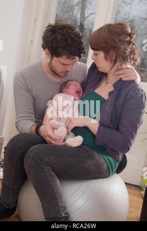 Junge Eltern halten ihre neugeborene Tochter im Arm, das Kind ist 12 Tage alt und schreit | young parents holding her new born baby in her arms - the