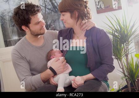 Junge Eltern halten ihre neugeborene Tochter im Arm, das Kind ist 12 Tage alt | young parents holding her new born baby in her arms - the baby ist 12