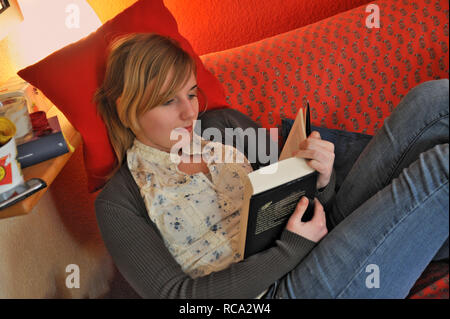 jugendliches Mädchen in ihrem Zimmer liest ein Buch   young female teenager in her room reading a book - Stock Photo
