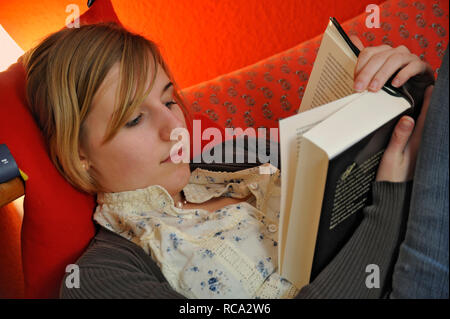 jugendliches Mädchen in ihrem Zimmer hört Musik mit MP3-Player | young female teenager in her room listening music from an MP3 player - Stock Photo